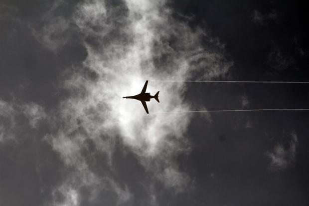 A US-led coalition plane flies above the Syrian border town of Kobane/Ayn al-Arab on 23 October, 2014 (AA)