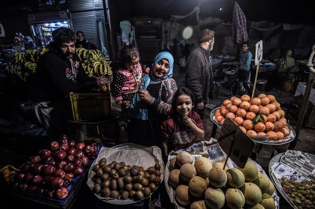 Egyptians smile for a photo as they buy fruit from a street vendor at a market in the Menufiya province, north of Cairo, on 22 February 2018 (AFP)