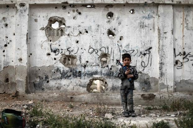 A Syrian boy stands with a toy gun in front of a bullet-riddled wall in the rebel-held town of Douma (AFP)