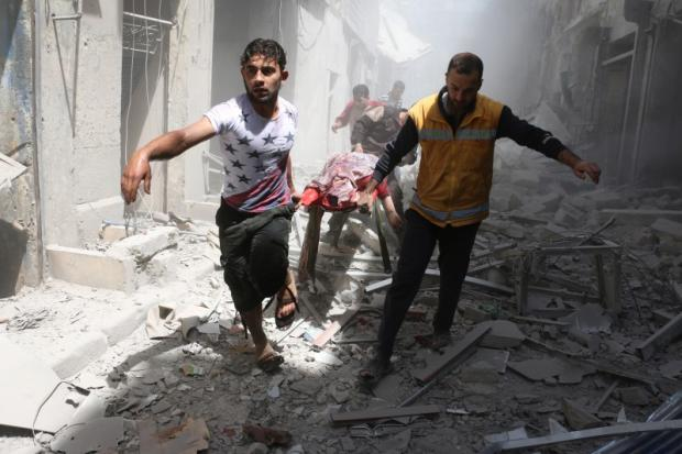 Men carry body on stretcher amid rubble of destroyed buildings after airstrike on rebel-held neighbourhood in Aleppo (AFP)