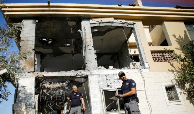 Israeli sappers work on a house in Beersheba that the Israeli military said was hit by a rocket fired from the Gaza Strip
