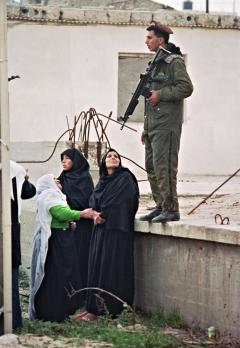 Palestinian women argue with an Israeli soldier (r) as they line up outside Ansar II prison camp in Gaza in February 1988, to visit their sons, held prisoners (AFP)