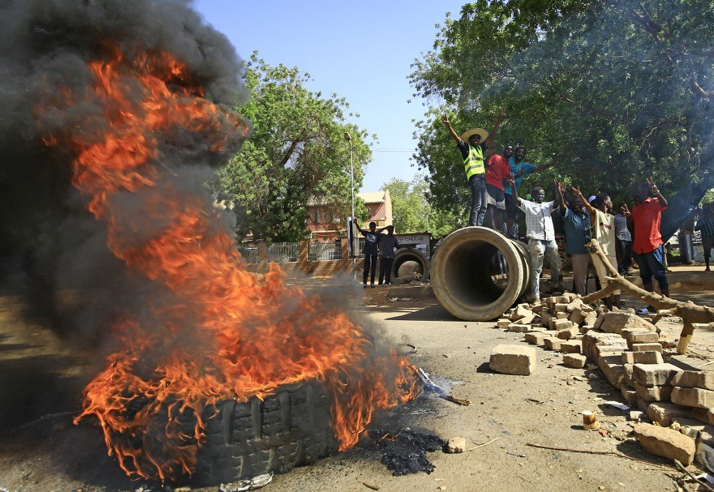 Sudanese protesters burn tyres in Khartoum on 13 May (AFP)