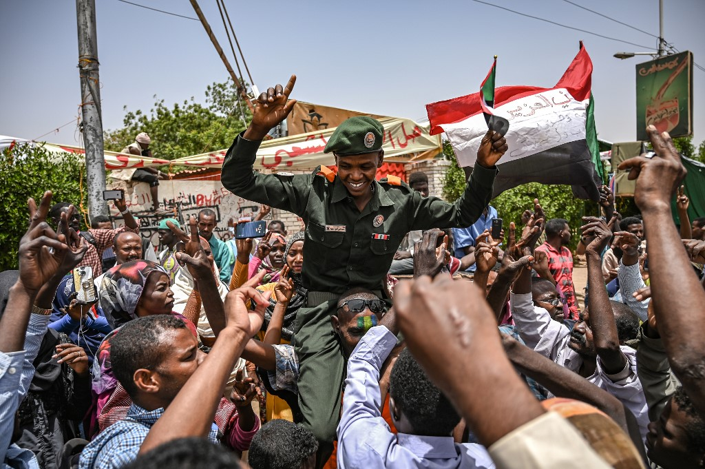 A Sudanese soldier joins protesters in Khartoum on 18 April (AFP)