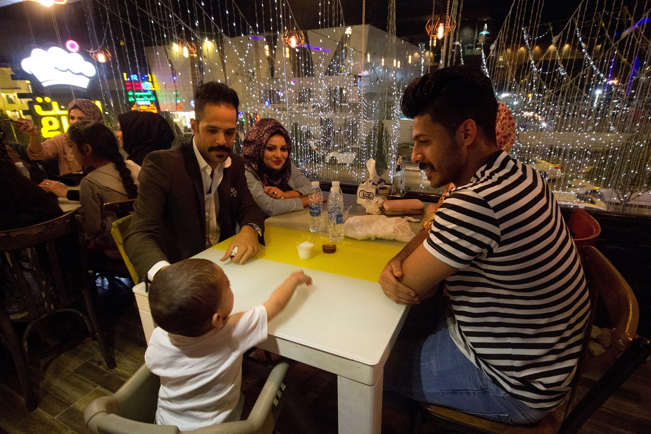 A family enjoying a meal at a Syrian restaurant in Mansour, Baghdad (MEE/Charlotte Mayhew)