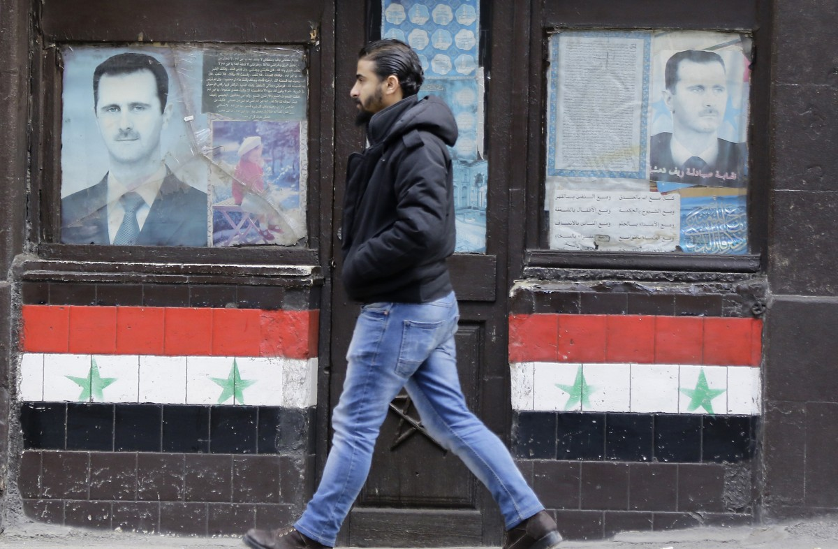 A Syrian man walks past posters of Syrian President Bashar al-Assad on a shop front in the capital Damascus on January 3, 2017 (AFP)