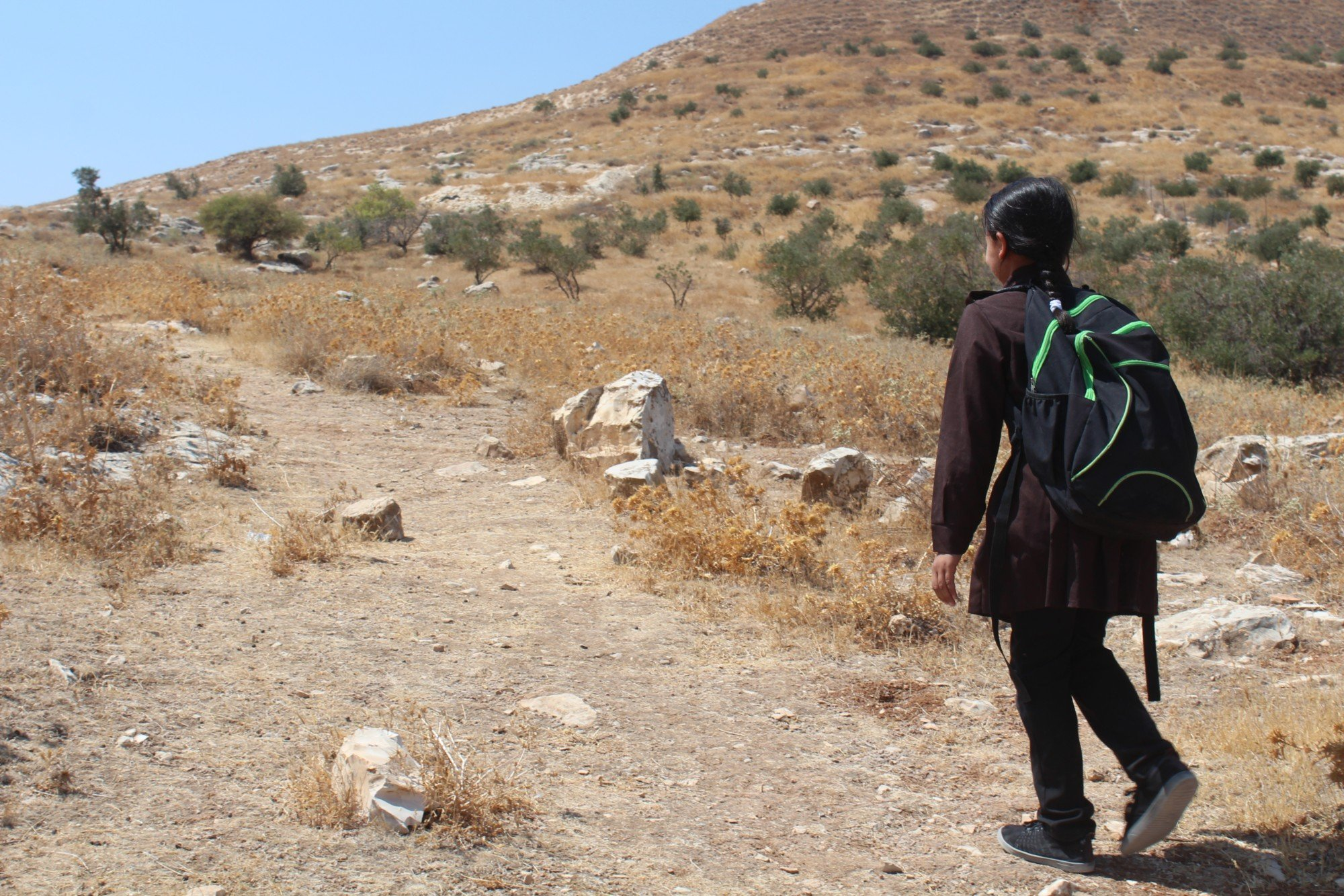Ibtisam, like many other children in Area C, has to walk on craggy dirt roads to go to school (MEE/Shatha Hammad)
