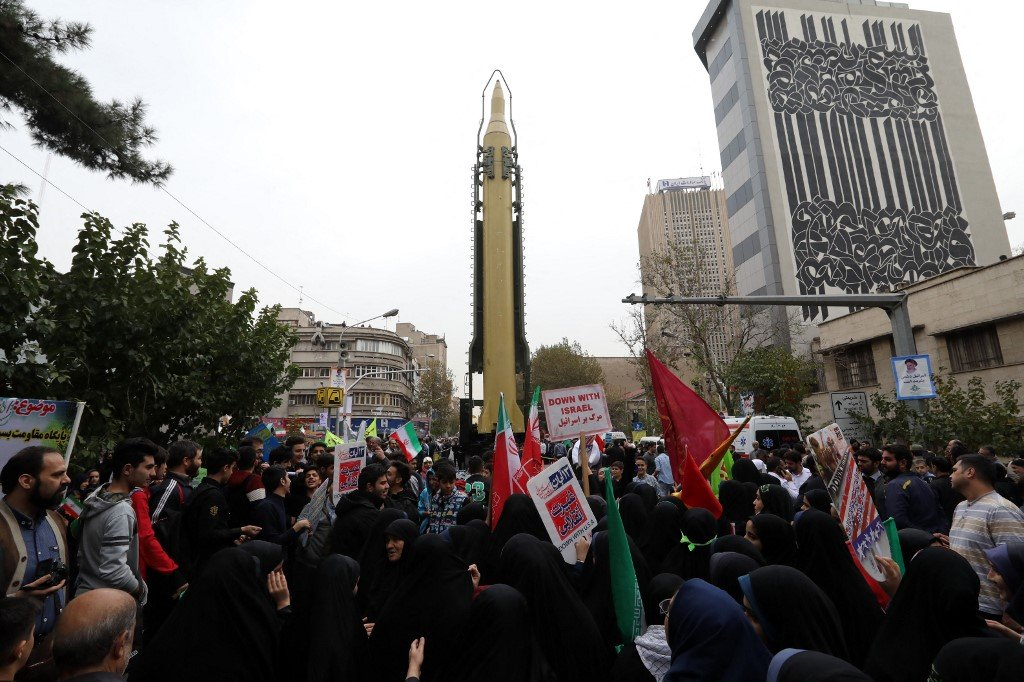 Iranians gather next to a replica of a Ghadr medium-range ballistic missile during a demonstration outside the former US embassy in Tehran in 2017 (AFP)