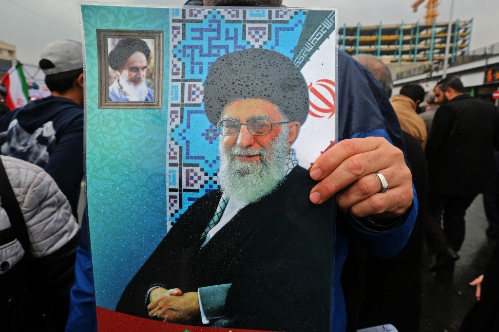 An Iranian holds up a portrait of Supreme Leader Ali Khamenei, with a smaller corner portrait of Ayatollah Khomeini, in Tehran on 11 February (AFP)