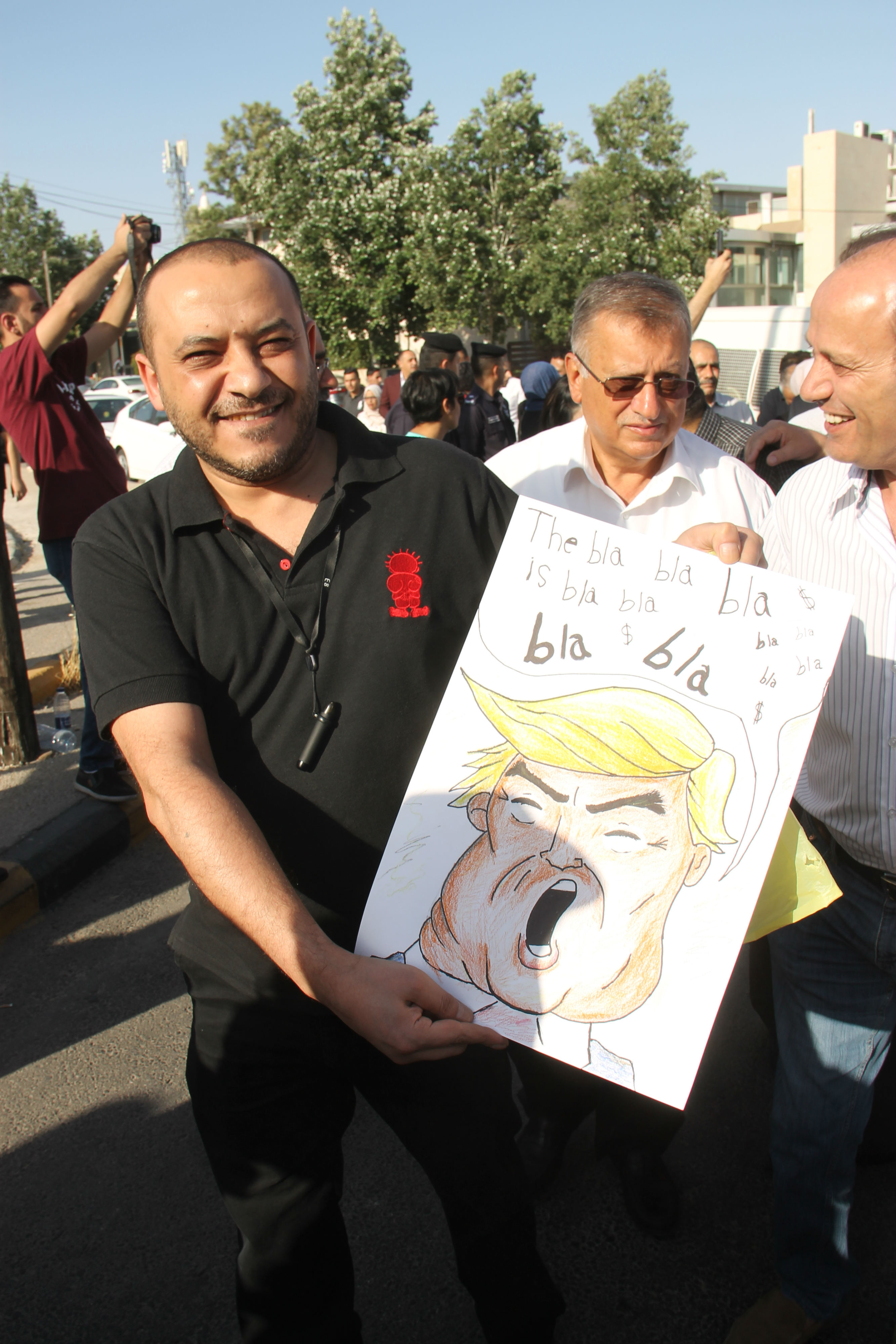 "A protester holds an image of Donald Trump at a rally against his ""deal of the century"" in Amman (MEE/Mohammed Ersan)"