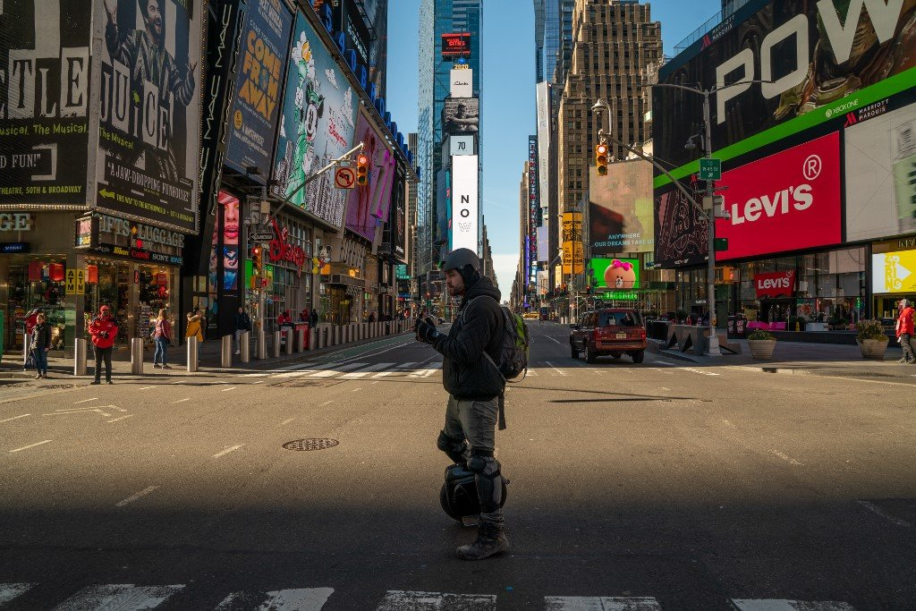 A person walks through a nearly empty Times Square in New York City on 12 March (AFP)