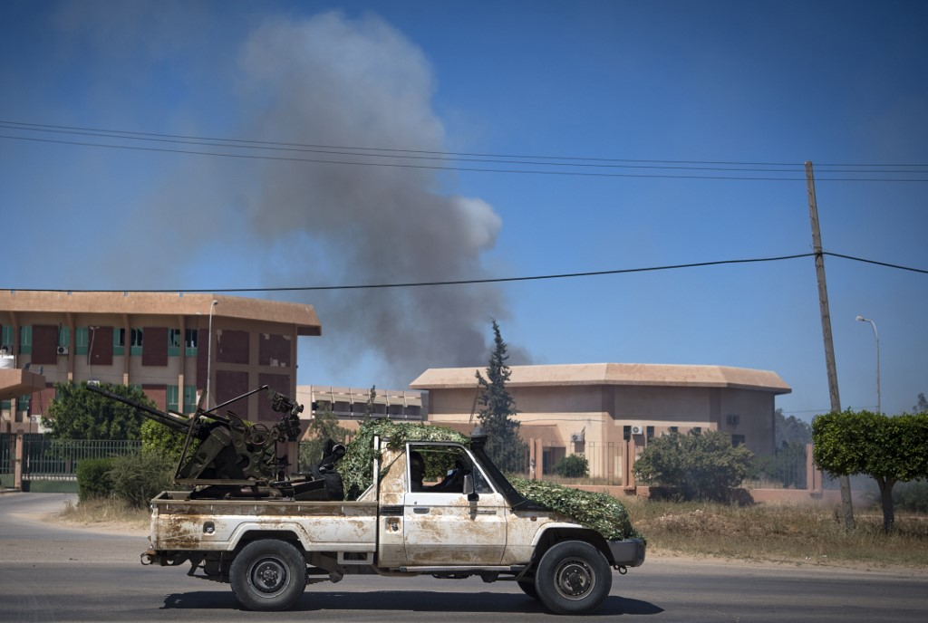 Smoke rises above buildings south of Libya's Tripoli on 29 April (AFP)