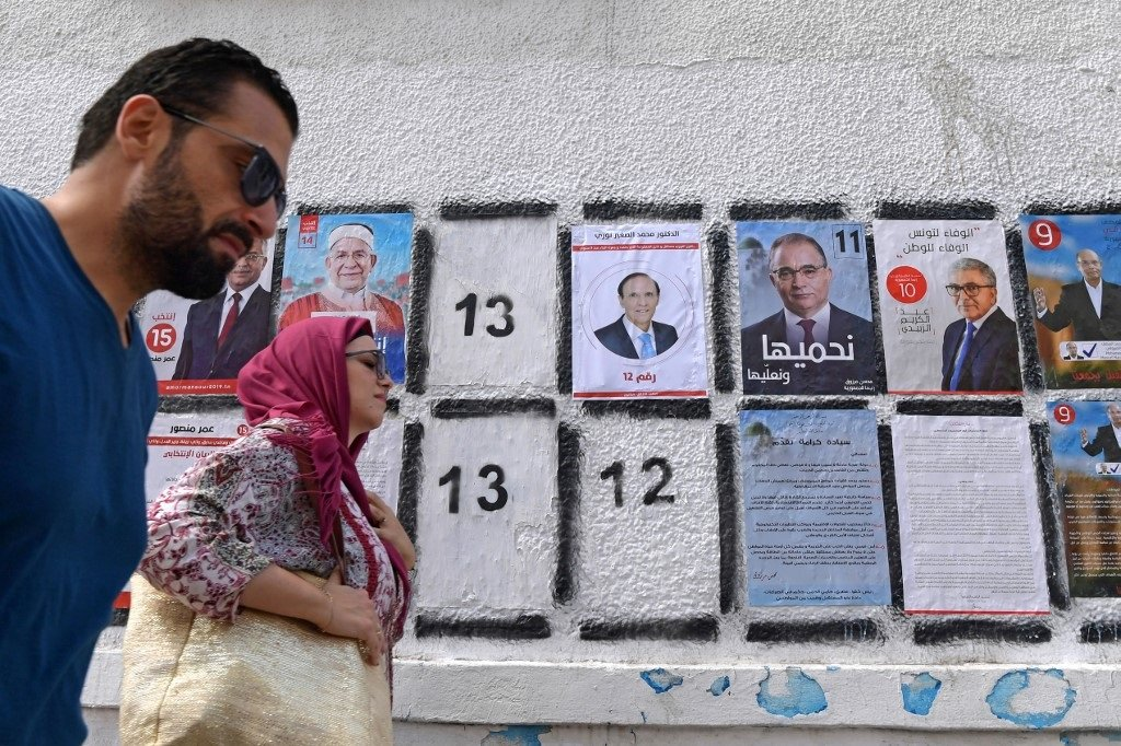 Posters of some of the 26 presidential candidates posted in Tunis (AFP)