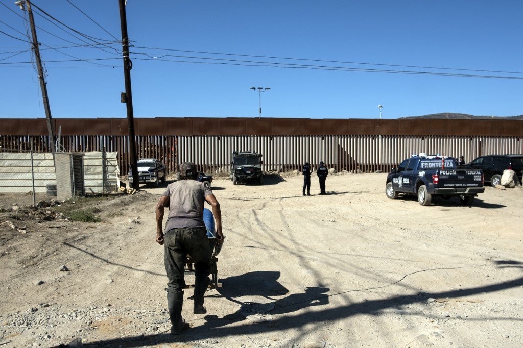 Mexican security forces guard the US-Mexico border fence on 18 September (AFP)