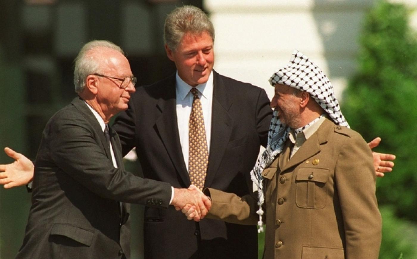 Le président américain Bill Clinton (centre), le Premier ministre israélien Yitzhak Rabin et le président de l'OLP Yasser Arafat signent le 1er accord d'Oslo à Washington le 13 septembre 1993 (AP)