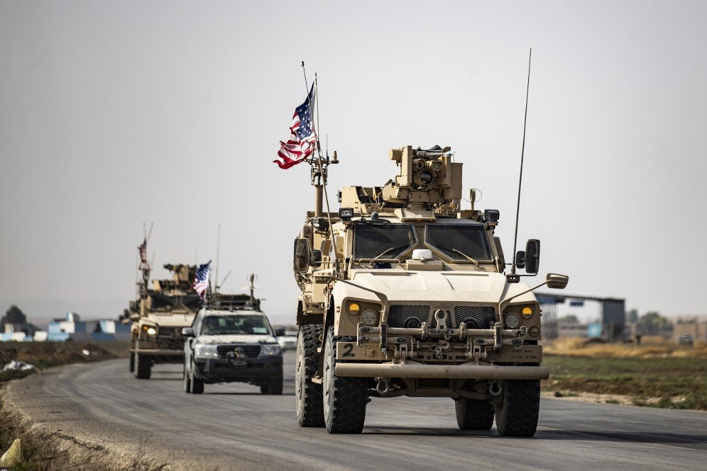 US military vehicles traverse the northern Syrian town of Tal Tamr on 20 October (AFP)