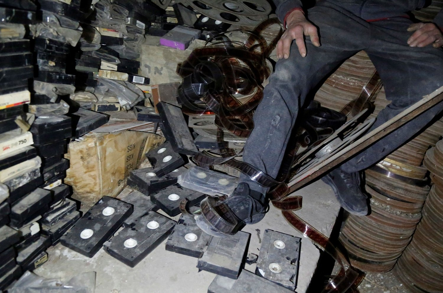 The shells of dust-encrusted videotapes, which also played at the cinema during its heyday, crack and crumple under foot on the floor of the store room. (Reuters)