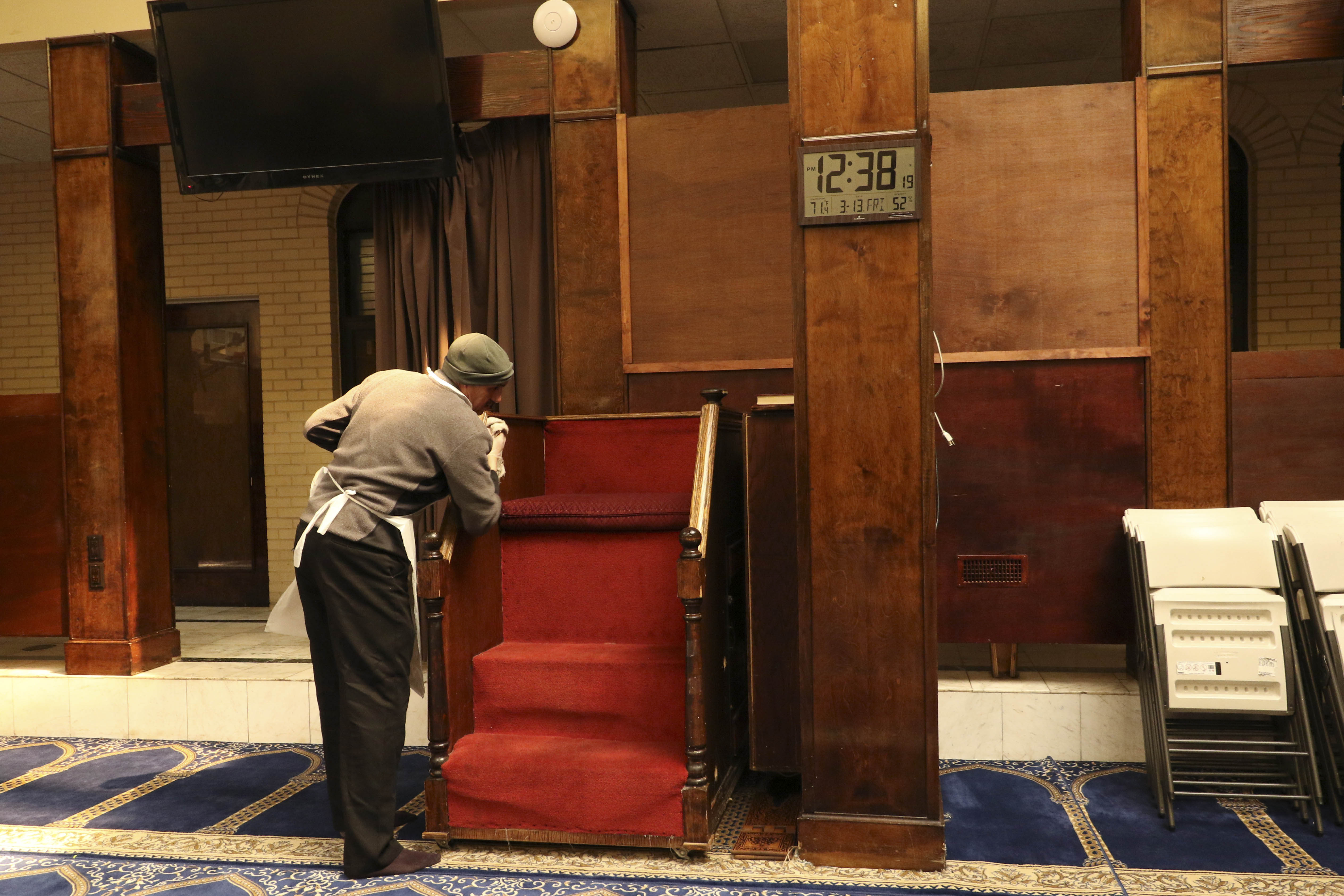 A man is cleaning the inside of the mosque.