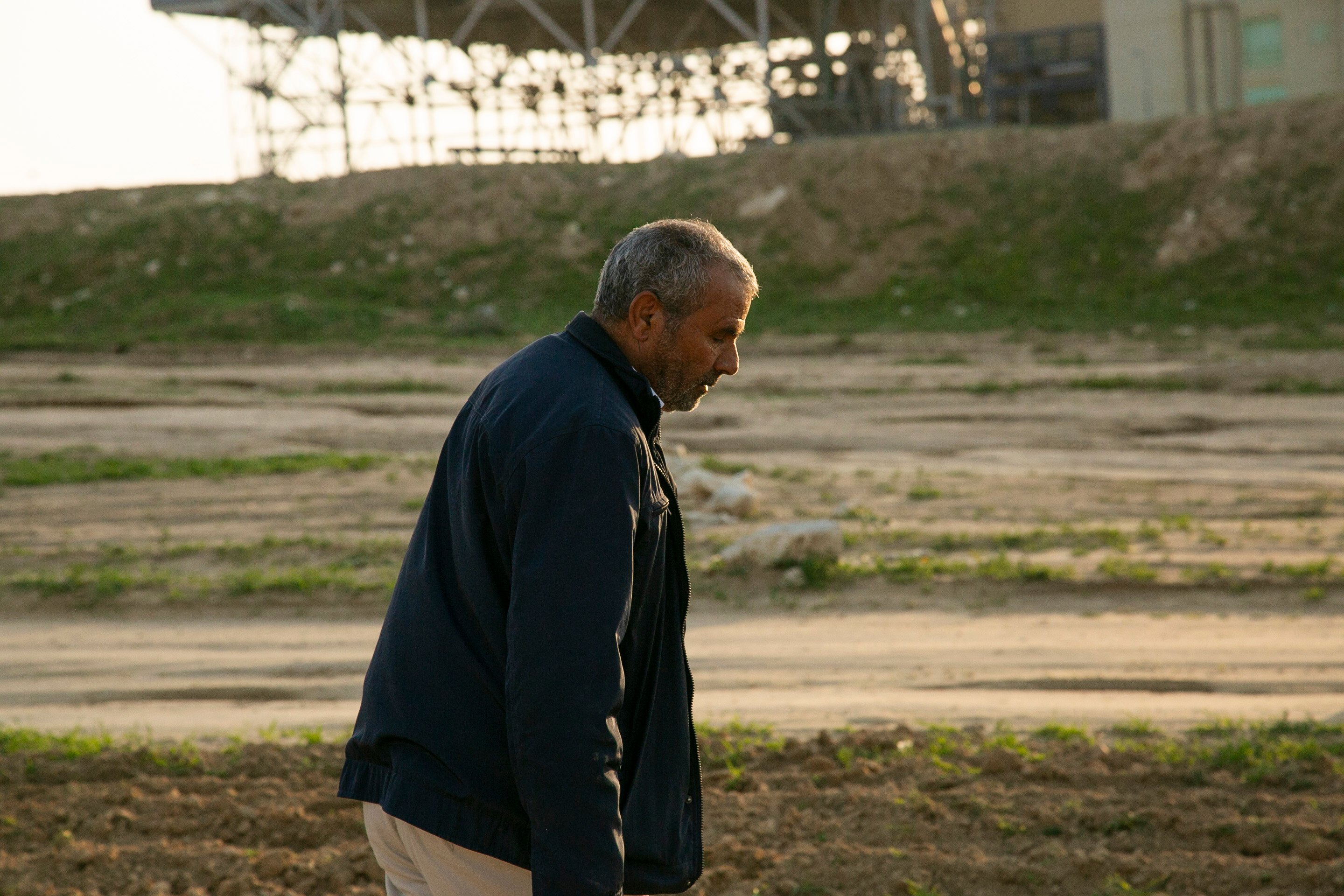 Me'eqel Al Hawashla inspects the damage to Wadi al Na'am's agricultural land (MEE/Jack Dodson)