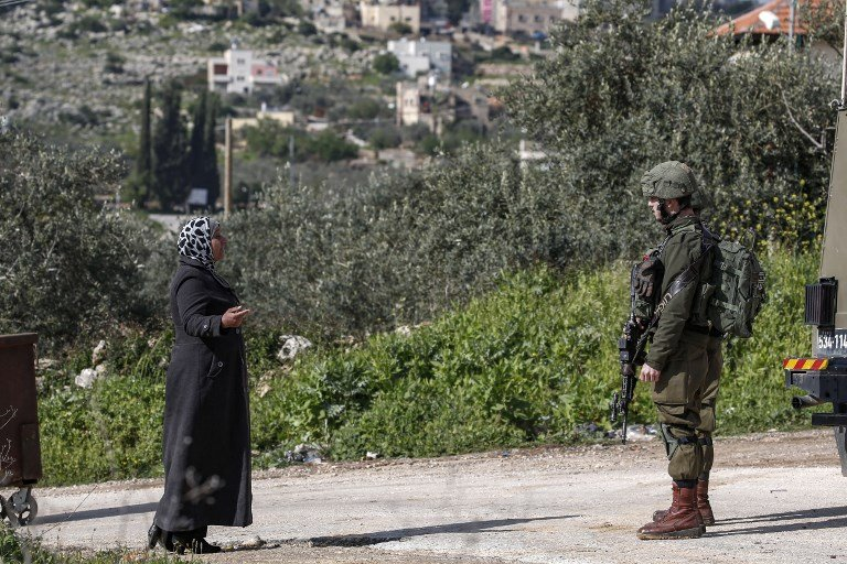 A Palestinian woman speaks with an Israeli soldier at a West Bank checkpoint on 17 March (AFP)