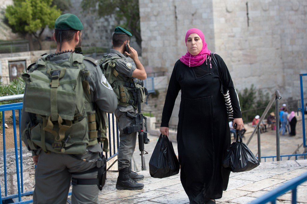 A Palestinian woman walks past Israeli border police at an entrance to the Old City in East Jerusalem (AFP)