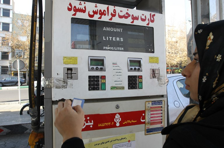 An Iranian woman uses a fuel smart card at a gas station in Tehran (AFP)