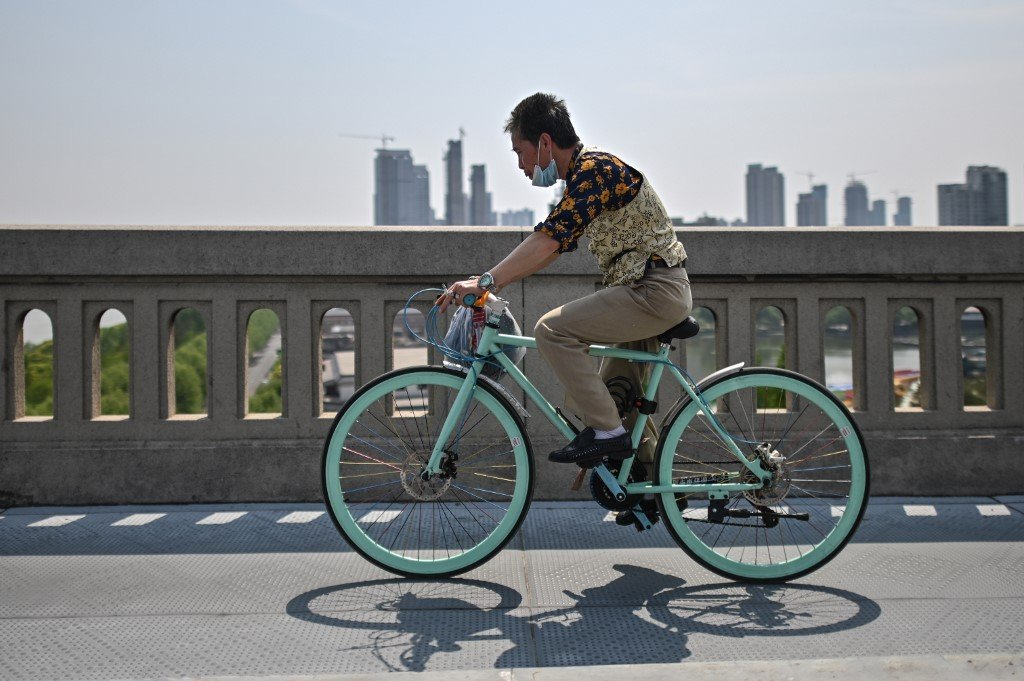 A man wearing a face mask rides a bicycle on Wuhan Bridge over the Yangtze river in Wuhan, China's central Hubei province on April 16, 2020. (AFP)
