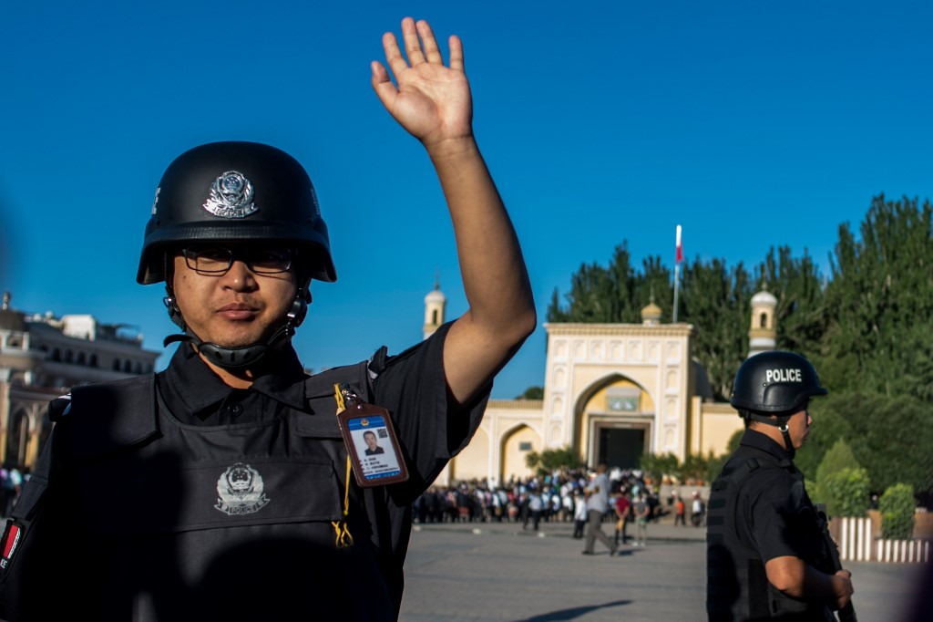 A police officer gestures as Muslims arrive at a mosque in the Xinjiang region in 2017 (AFP)