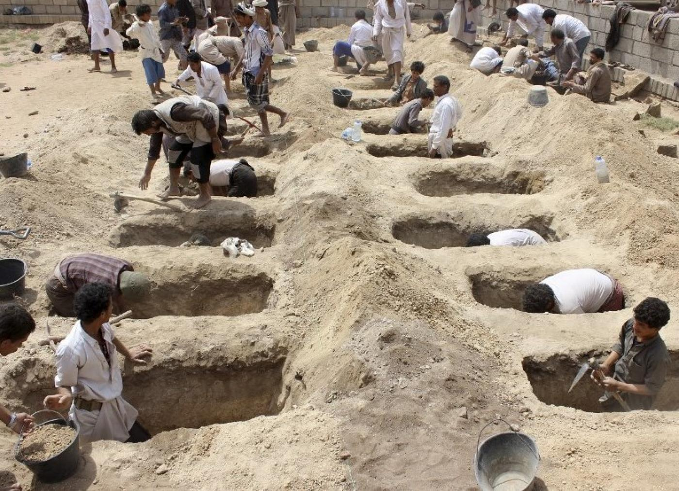 Yemenis dig graves for children, who where killed when their bus was bombed by Saudi-led coalition (AFP)