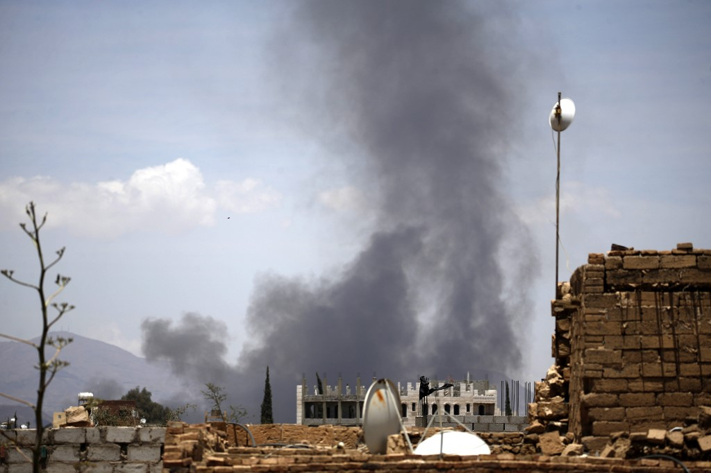 Smoke billows after an air strike by the Saudi-led coalition in Sanaa in 2018 (AFP)